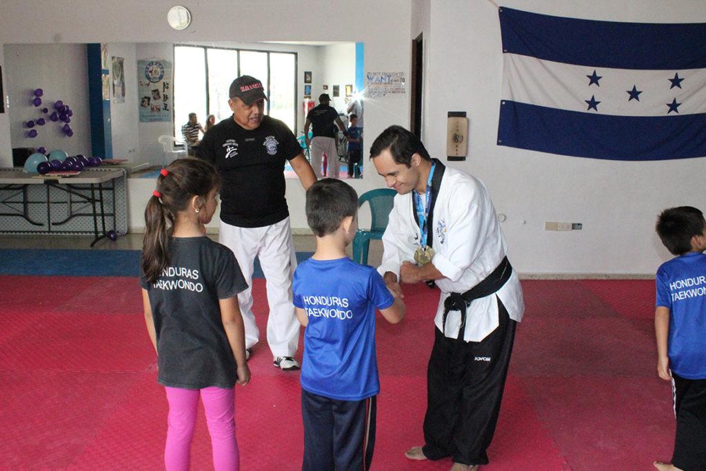Junior comienza la felicitación a los nuevos cinturones blancos de la academia. Foto HSI